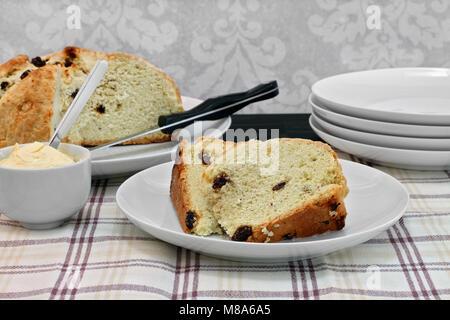 Tabelle mit einem Laib des irischen Soda Brot mit Slices auf einer Platte vor. Seite von Schlagsahne Butter. - Stockfoto