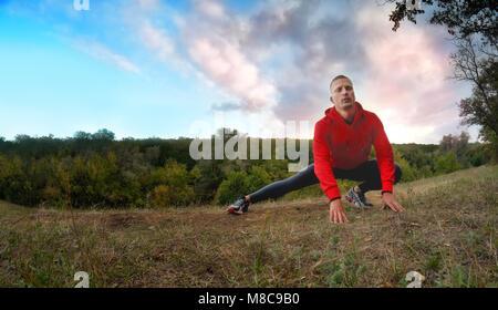 Eine junge starke athletischen Mann im roten Mantel mit Kapuze und schwarz Sport leggins führt Warming-up mit Beinen - Stockfoto