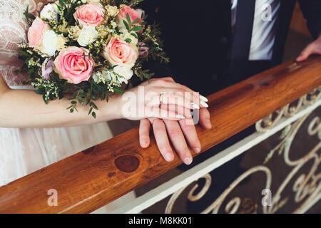 Die Braut und der Bräutigam halten das Geländer auf der Treppe. Trauringe der Jungvermählten close-up. - Stockfoto