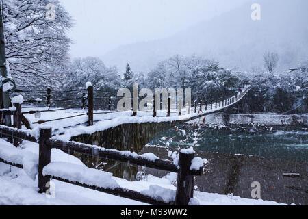Gifu, Japan - Dezember 12, 2013: Touristen zu Fuß auf Holzbrücke in Shirakawago, World Heritage Village, das Reiseziel, im Winter mit Sno - Stockfoto