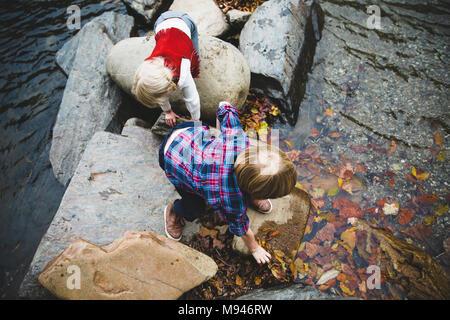Kinder spielen auf den Felsen am Fluss - Stockfoto