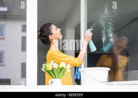 Lächelnde Frau zu Hause Reinigung der Fenster - Stockfoto