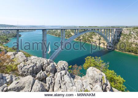 Eine Autobahn Brücke über den Fluss Krka in der Nähe der Stadt Trogir, Šibenik-Knin, Kroatien. Segelboote Segeln auf dem Fluss. - Stockfoto