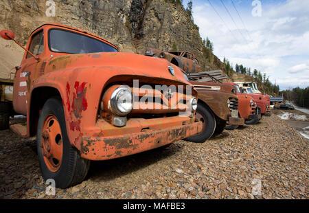 Eine alte, Rot 1955 Ford F-500 Truck unter einer Reihe von alten Fahrzeugen, die in einem Steinbruch, östlich von Clark Gabel Idaho. - Stockfoto