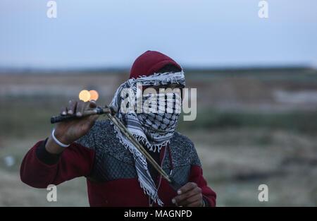 Gaza, den 2. April 2018. Eine maskierte Palästinensischen Demonstrant hält seine Steinschleuder bei Auseinandersetzungen mit israelischen Truppen entlang der Grenzen zwischen Israel und dem Gazastreifen, im Osten von Gaza, Gazastreifen, 02. April 2018. Foto: Wissam Nassar/dpa Quelle: dpa Picture alliance/Alamy leben Nachrichten - Stockfoto