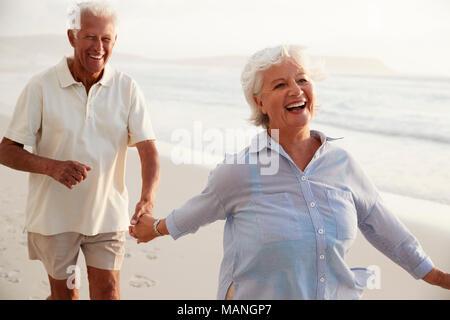 Älteres Rentnerehepaar Entlang Strand Hand in Hand zusammen - Stockfoto