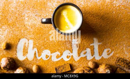 Eine Tasse Kaffee, Kakao oder eine heiße Schokolade auf dem Hintergrund der Aufschrift Schokolade aus Kakao unter Schokolade Süßigkeiten. Ich liebe Schokolade Konzept - Stockfoto