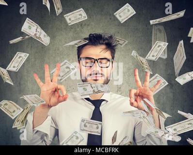 Business Mann in Gläser meditieren unter Geld Regen - Stockfoto