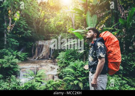 Stehende Person im Wasserfall, inspiriert Happy Traveler Natur genießen, Abenteuer Konzept - Stockfoto