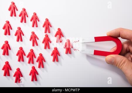 Nahaufnahme einer menschlichen Hand zieht Rot menschliche Figuren mit Hufeisen Magnet auf weißem Hintergrund - Stockfoto