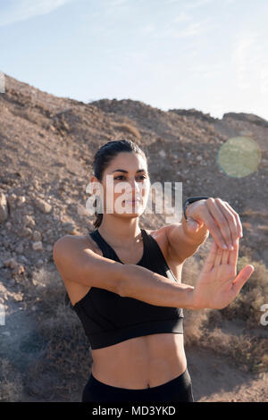 Junge weibliche Läufer stretching Arms in ariden Landschaft - Stockfoto