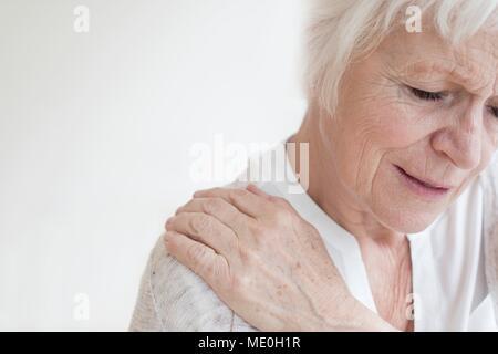 Ältere Frau reiben wunde Schulter. - Stockfoto