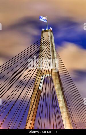 Beleuchtete Mast und Bogen, den die ANZAC Bridge in Sydney mit der australischen Flagge im Wind bei Sonnenuntergang gegen Wolken und blauer Himmel - Stockfoto