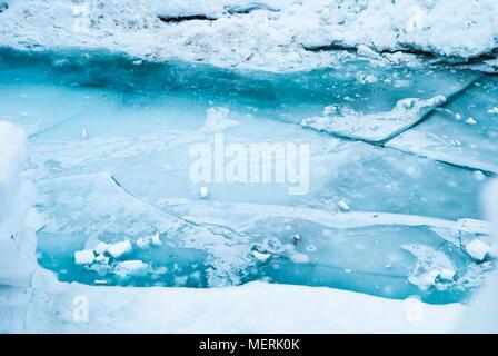 Die großen blauen Risse im Eis auf dem Fluss. - Stockfoto