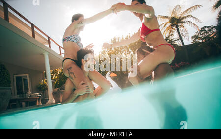 Frauen sitzen auf ihre Freunde Schultern im Pool. Freunde spielen in einem Pool. - Stockfoto