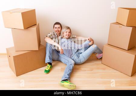Bild von Mann und Frau sitzen auf dem Boden der Kartons - Stockfoto