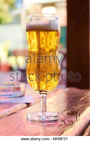 Gläser Bier auf dem Tisch zu stehen in einem Garten Pub auf ein Sommer sonnigen Tag mit einem unscharfen Hintergrund - Stockfoto