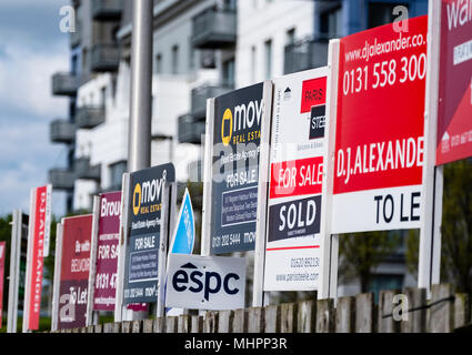 Viele Boards von Immobilien zum Verkauf und zur Miete außerhalb große, moderne Apartment Blocks an der westlichen Hafen von Leith, Edinburgh, SCO - Stockfoto