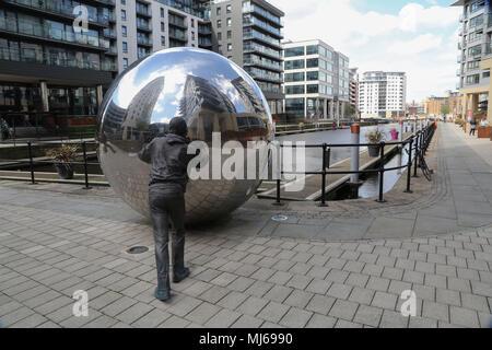 Eine reflektierende Ansatz ist eine zweiteilige Skulptur bestehend aus 2 lebensgroßen Bronzefiguren sie zwei reflektierende Edelstahl Kugeln auf einem Kanal. - Stockfoto