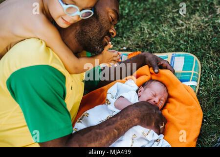 Sohn lehnt sich auf die Schulter des Lügens Vati, der an seinem neugeborenen Kind - Stockfoto