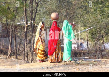 DAHMI KALAN - Indien, Januar 13, 2018: Drei junge Rajasthani Frauen in bunten Saris diskutieren in der Nähe von einem Brunnen beim Füllen der Krüge mit Wasser - Stockfoto