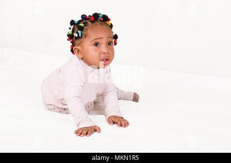 Foto von einer Pretty Baby von der Kamera sitzen auf weißem Hintergrund erschrocken. - Stockfoto