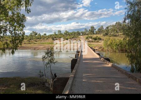 Lange niedrigen schmalen konkrete Brücke über das ruhige Wasser von Bowen Fluss mit Kies Straße durch Buschland unter blauem Himmel in Qld Australien - Stockfoto