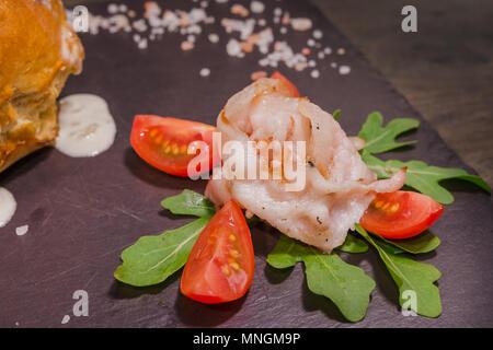 Frische Erbsensuppe in einem Brot Schüssel, auf einem Holzbrett mit Salz und Papper - Stockfoto