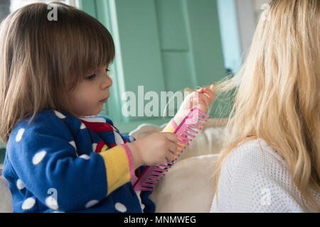 Kleines Mädchen (2-3) die Haare kämmen, Mutter - Stockfoto