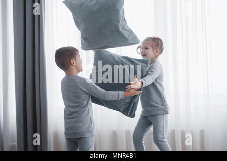 Kleine Jungen und Mädchen inszenierten eine Kissenschlacht auf dem Bett im Schlafzimmer. Freche Kinder schlagen einander Kissen. Sie mögen diese Art von Spiel - Stockfoto
