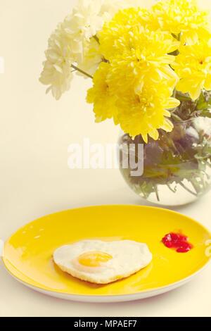 Frühstück. Spiegelei in einer herzförmigen Blumenstrauß aus Chrysanthemen in der Nähe von - Stockfoto