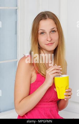 Mädchen in ein rosa Kleid mit gelben Glas in der Hand zu Hause in der Nähe eines Fensters - Stockfoto