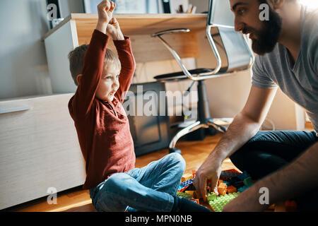 Vater und Sohn auf dem Boden zu Hause sitzen zusammen spielen mit Bauklötzen - Stockfoto