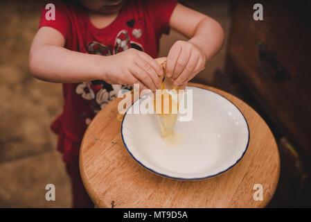 Ein Kleinkind ein Bauernhof frisches Ei in eine Schüssel geben. - Stockfoto