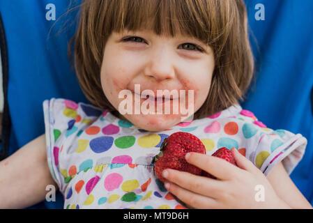 Ein 3 Jahre altes Kleinkind isst eine Erdbeere. - Stockfoto