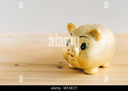 Goldene Sparschwein auf hölzernen Schreibtisch - Stockfoto