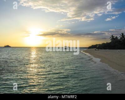 Sonnenuntergang über dem tropischen Meer und Coral Beach mit bunten Wolken im Himmel. Boote am Horizont. Nord Male Atoll Asdu, Indischer Ozean. - Stockfoto