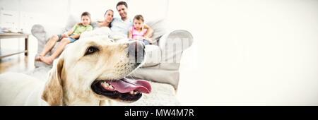Glückliche Familie sitzen auf der Couch mit ihrem Haustier gelbe Labrador im Vordergrund - Stockfoto