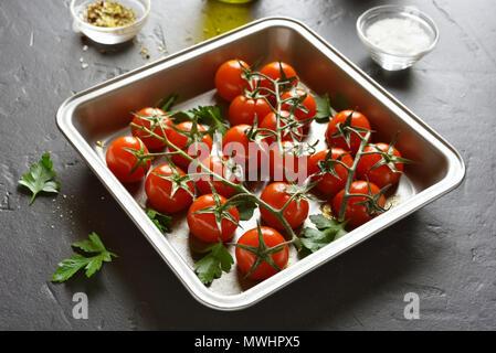 Leckere gebackene Kirschtomaten in Backblech auf schwarzen Stein Tabelle - Stockfoto