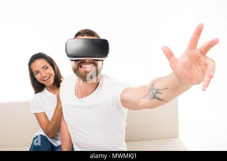 """""""Porträt der jungen glücklich Mann sitzt auf einem Sofa mit Virtual reality Headset mit Freundin hinter sitzen, isoliert auf weißem - Stockfoto"""