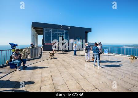Gibraltar, UK - 18. Mai 2017: Touristen und Berberaffen auf der Aussichtsplattform auf der oberen Station der Seilbahn auf den Felsen von Gibraltar, Vereinigtes Königreich, W - Stockfoto