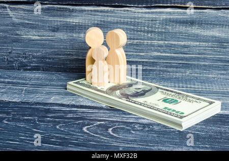 Personen und ein Kind stehen auf einem Haufen von Dollar. Die Leute stehen auf das Geld. Die Zahlung von Steuern, die Leistungen. Familie Ersparnisse, Investitionen in neue - Stockfoto