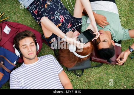 Freunde liegen auf Gras, mit Virtual reality Simulator und Hören mit Kopfhörern - Stockfoto