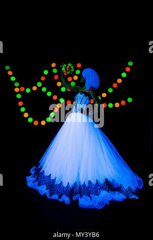 Hochzeit Foto Session der Braut mit Blumen Neon Fotografie farbenfrohe auf einem dunklen Hintergrund im ultravioletten Strahlen junge Mädchen im weißen Brautkleid im Trend Style posiert - Stockfoto