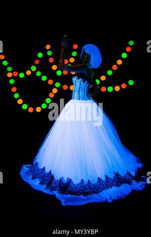 Hochzeit Foto Session der jungen Braut Neon Fotografie farbenfrohe auf einem dunklen Hintergrund im ultravioletten Strahlen junge Mädchen im weißen Brautkleid im Trend Style posiert - Stockfoto