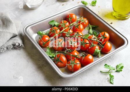 Gebackene Kirschtomaten in Backblech auf steinernen Tisch - Stockfoto