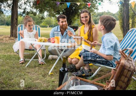 Engagierte junge Eltern von zwei Kindern hören auf Ihre lustigen Sohn sprechen beim zusammen essen während der Familie Picknick in einem Sommertag - Stockfoto