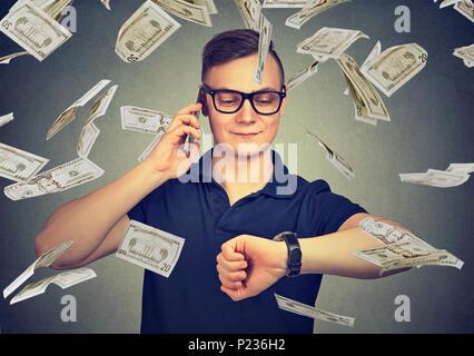 Besetzt Geschäftsmann an Armbanduhr suchen, Gespräch am Handy unter cash Regen. Zeit ist Geld Konzept - Stockfoto