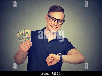 Fröhlich Inhalt junge Mann, der einfach Geld in kurzer Zeit an der Kamera schaut. - Stockfoto