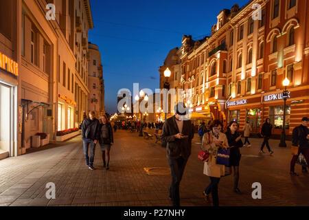 Moskau, Russland - 21. September 2017: Volk und historischen Gebäude, das von warmen Licht Arbat dekoriert Straße zu Fuß in der Dämmerung mit blauem Himmel. - Stockfoto
